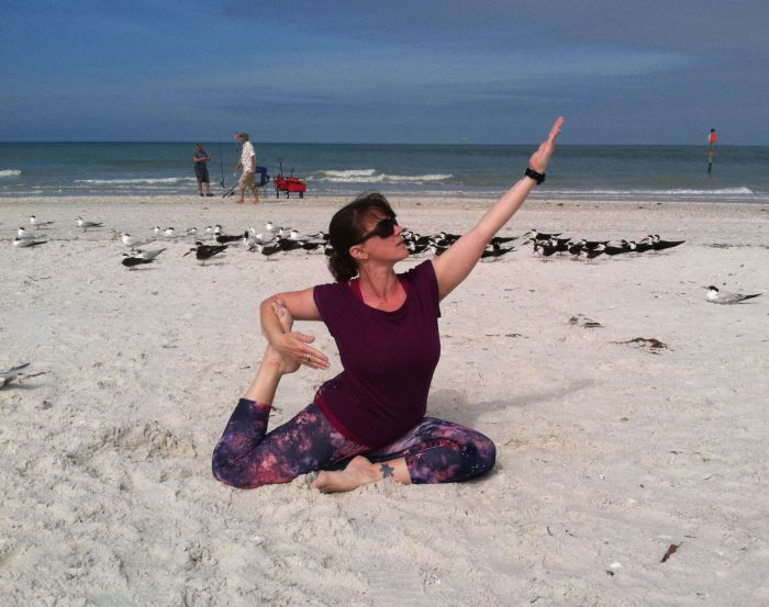 Yoga instructor Cara demonstrates a Pigeon Pose.